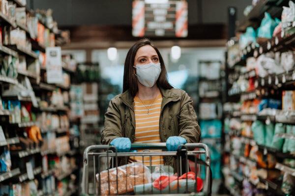 Woman pushing supermarket cart during COVID-19